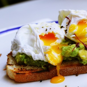 Poached egg with avocado on white plate
